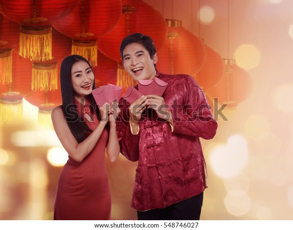 Chinese couple in cheongsam suit holding red envelope. Happy chinese new year concept