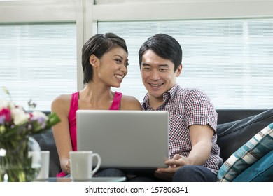 Chinese couple relaxing at home with a laptop on a sofa in their living room