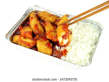 Chinese crispy battered chicken and rice with sweet and sour sauce in a foil take away tray isolated on a white background