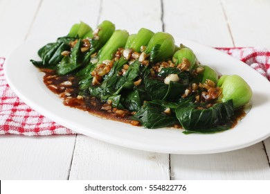 Chinese cuisine, Bok choy or chinese cabbage in oyster sauce and fried garlic, selective focus