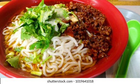 Chinese dan dan noodles in red bowl with green spoon