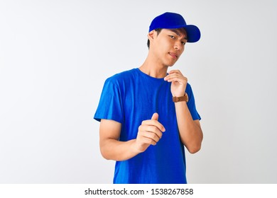 Chinese deliveryman wearing blue t-shirt and cap standing over isolated white background disgusted expression, displeased and fearful doing disgust face because aversion reaction. With hands raised