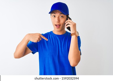 Chinese deliveryman wearing cap talking on the smartphone over isolated white background with surprise face pointing finger to himself