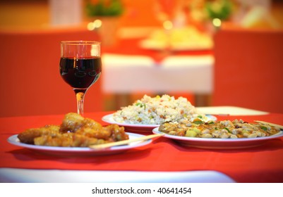 Chinese dinner with 3 dishes and wine glass