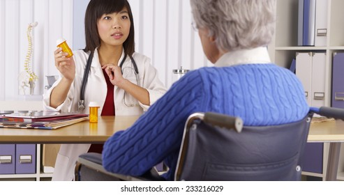 Chinese doctor talking about medication to elderly patient