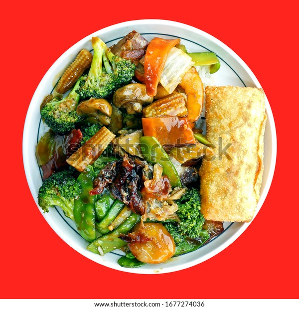 Chinese duck and shrimp with mixed fresh vegetables on a small white plate. Square composition, of mushrooms, broccoli, baby corn, a single egg roll, snow peas, and sauce on a red background.