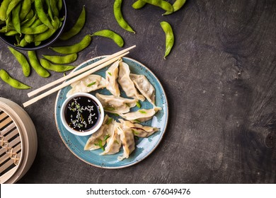 Chinese dumplings on plate, green boiled soybeans edamame, soy sauce and chopsticks background. Traditional Chinese/Asian dish. Dim sum dumplings ready to eat. Chinese cuisine concept. Space for text