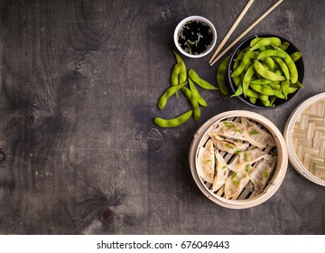 Chinese dumplings in rustic wooden bamboo steamer with green boiled soybeans edamame, soy sauce and chopsticks. Traditional Chinese/Asian dish. Space for text. Food background. Dim sum dumplings