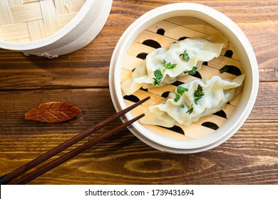 chinese dumplings in wooden steamer with chopsticks soy sauce Chinese Traditional cuisine concept Overhead. close up