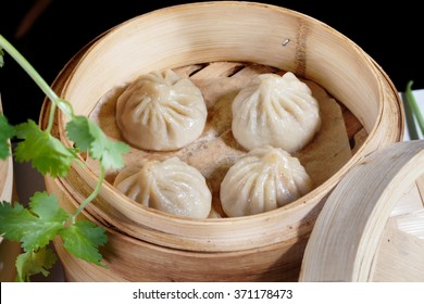 Chinese dumplings in a wooden steamer in the still life on a table the national atmosphere of great food