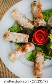 Chinese egg rolls (spring rolls) with salad on plate. Restaurant