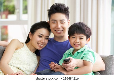 Chinese Family Sitting And Watching TV On Sofa Together