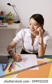 Chinese fashion designer smiling, sketching at work desk