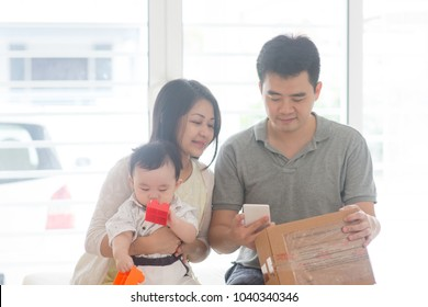 Chinese father scanning QR code with smart phone. Happy Asian family at home, natural living lifestyle indoors.