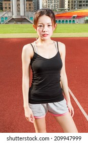 Chinese female jogger standing on sports field looking at camera