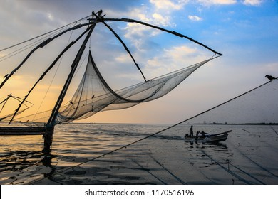 Chinese fishing nets in evening against setting Sun and boats,famous tourists location at Fort Cochin,Kerala ,India