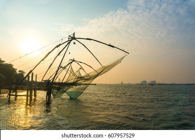 Chinese fishing nets on the shore of the Arabian Sea. Fort Cochin, Kerala, India. Historic Landmark. Warm evening. Scenic contours in the sunset twilight. Bright solar disk. Delicate juicy colors.