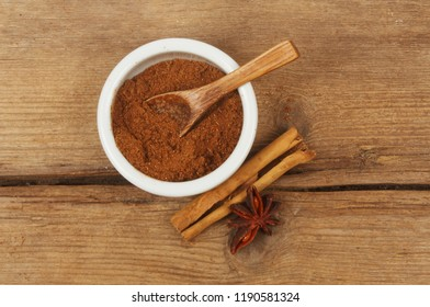 Chinese five spice in a ramekin with cinnamon and star anise on weathered wood