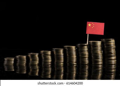 Chinese flag with lot of coins isolated on black background