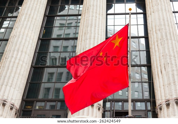Chinese flag floating in front of a government building