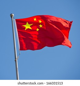 Chinese flag with flag pole waving in the wind over blue sky background.