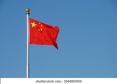 Chinese flag waving in the wind with clear blue sky