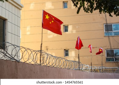 Chinese flags on barbed wired wall in Kashgar (Kashi), Xinjiang, China.