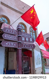 Chinese flags over Uigher street signs in Old City Kashgar, or Kashi, Xinjiang, China.