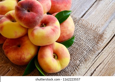 Chinese flat donut peaches with leaves on on old wooden table also known as  Saturn donut, doughnut,paraguayo,pan tao peach.