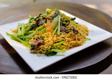 Chinese food - Beef lo mein meal on white square plate