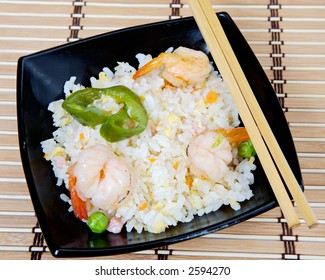 Chinese food in a black plate and sticks