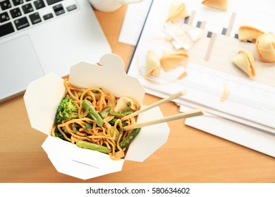 Chinese food box on the office desk. Eating at the office. Overtime work concept. Top view. Daylight. Horizontal