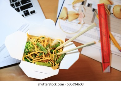 Chinese food box on the office desk. Eating at the office. Overtime work concept. Top view. Horizontal