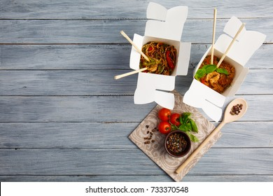 Chinese food in a box on a wooden table. Chinese and Asian fast food.