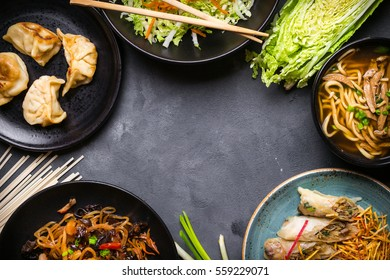 Chinese food dark background. Chinese noodles, fried rice, noodle soup, dim sum, spring rolls, salad. Traditional Chinese cuisine dishes set. Space for text. Top view. Chinese restaurant concept