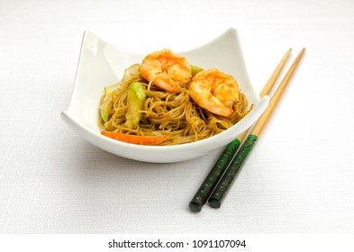 Chinese food, fried rice noodles with shrimps and vegetables served in a bowl with chopsticks