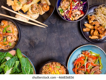 Chinese food on black background. Noodles, fried rice, dumplings, stir fry chicken, dim sum, spring rolls, bean sprouts, bok choy. Chinese cuisine set. Space for text. Top view. Chinese restaurant