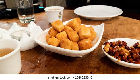 Chinese food on a table including roasted peanuts and fried tofu with a cup of tea and glass of water