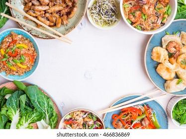 Chinese food on white background. Noodles, fried rice, dumplings, stir fry chicken, dim sum, spring rolls, bean sprouts, bok choy. Chinese cuisine set. Space for text. Top view. Chinese restaurant