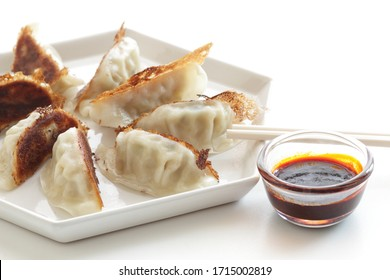 Chinese food, pen fried  jiaozi for dumpling dish served with hot chilli pepper sauce