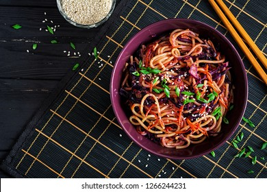 Chinese food. Vegan stir fry noodles with red cabbage and carrot in a bowl on a black wooden background. Asian cuisine meal. Top view