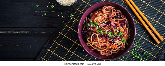 Chinese food. Vegan stir fry noodles with red cabbage and carrot in a bowl on a black wooden background. Asian cuisine meal. Banner. Top view