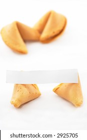 Chinese Fortune Cookie open with blank paper, on white background, two unopened in background