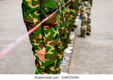 Chinese freshmen college students are lining up while standing still during military training at school with pink ribbon
