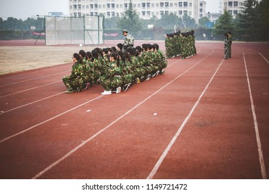 Chinese freshmen college students are sitting still during military training at school. view from the back