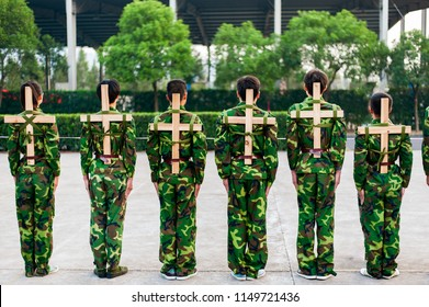 Chinese freshmen college students are standing stand still during military training at school with wooden crosses at their back