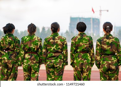 Chinese freshmen college students are standing stand still during military training at school. view from the back