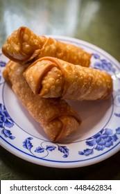 Chinese fried crispy egg rolls on fancy dinner plate