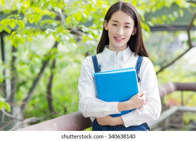chinese girl embrace textbooks, standing under a tree shade