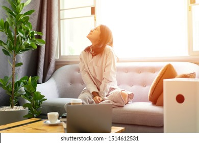 chinese girl feeling fresh and happy with good climate on sofa and laptop computer and air purifier